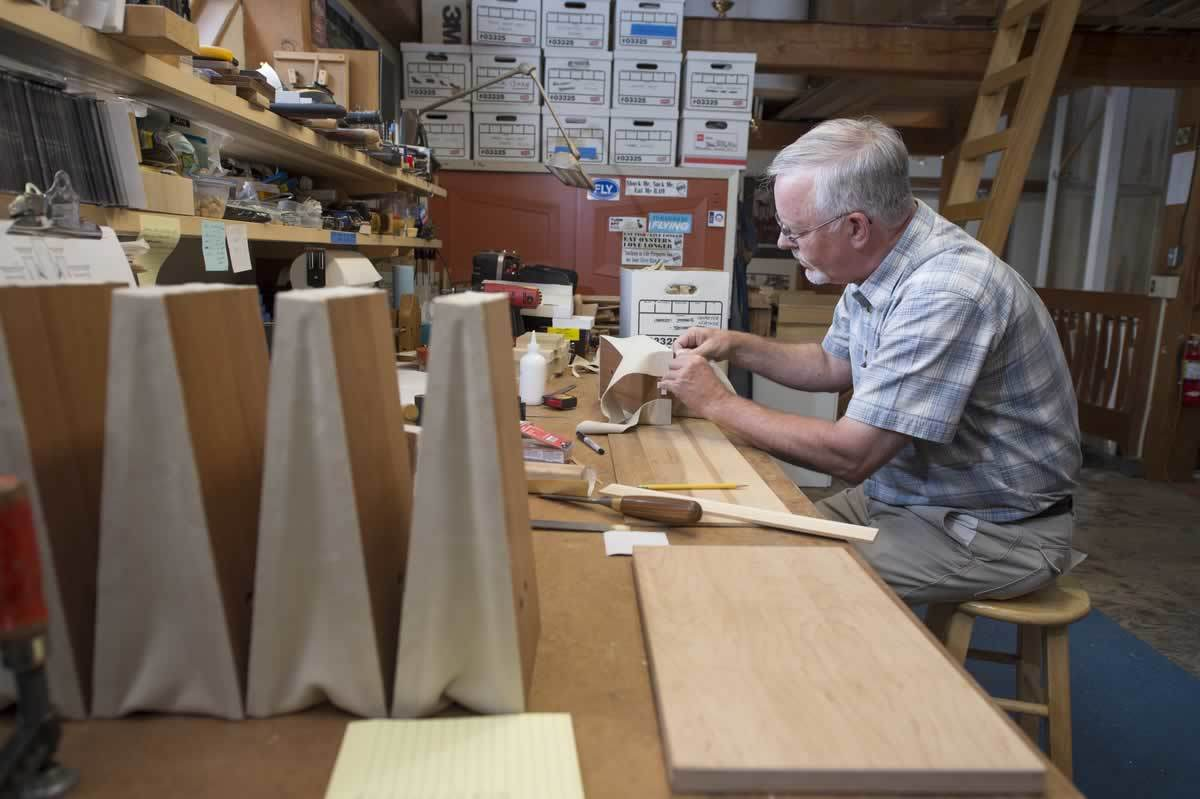 The workshop's assistant director, Bruce Shull, leathers the concussion bellows he's made piece by piece at his workbench. The devices can be installed as needed to manage windflow in the finished instrument.