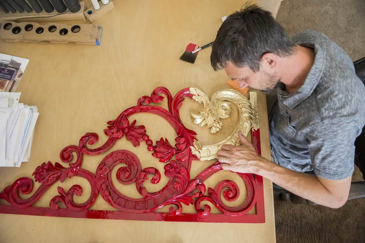 "Andreas Schonger applies 23-karat gold leaf or ""gilding"" to a segment of decorative screen carved for the basilica organ project by a woodworker in Germany."