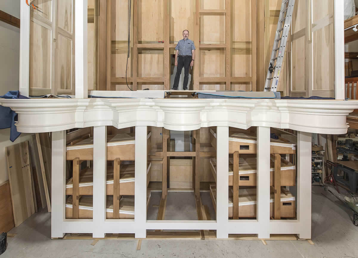 "Paul Fritts stands inside the case of the new pipe organ for the Basilica of the Sacred Heart as it appeared in July 2015. The ""set-up room"" is the first thing visitors see when they enter the workshop at Paul Fritts & Company Organ Builders in Tacoma, Washington."