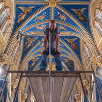 On Monday morning, rigger Joshua Wood of Organ Clearing House awaits the next section of framing as he builds a scaffold inside the basilica.