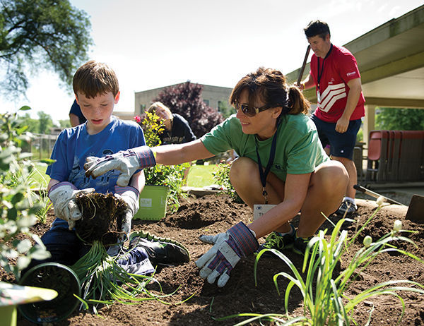 During the 2013 family camp, Theresa McKenna '89 and her son, Carter, planted flowers at South Bend's Healthwin Hospital.<br />  photo: Matt Cashore '94
