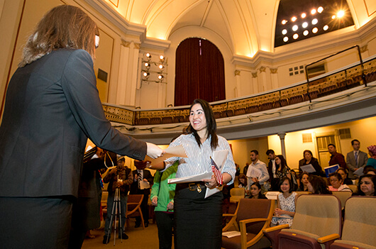 Haruethi Francis, originally from Thailand, picks up paperwork after the naturalization ceremony on April 18 at Washington Hall, photo by Becky Malewitz, South Bend Tribune