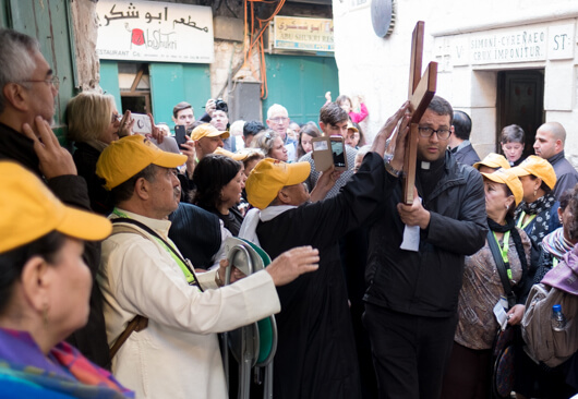 Egyptian pilgrims reach to touch the cross as Pastor Ashraf Tannous of the Lutheran Church of Beit Sahour leads a walk of the Via Dolorosa on Good Friday, photo by Ben Gray