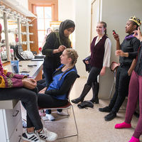 With makeup and music, cast members prepare to take the stage.