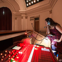 From the balcony at Washington Hall, director Christy Burgess works sound and lights as she watches the performance.