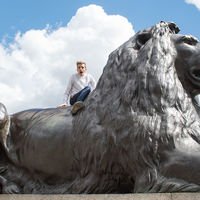 Robinson Shakespeare Company ensemble member Forest Wallace rides a lion in London's Trafalgar Square.