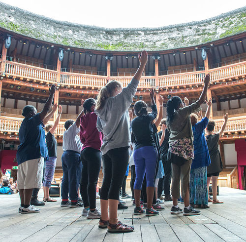 Robinson Shakespeare Company ensemble members raise their swords during a movement workshop on the stage at Shakespeare's Globe in London.